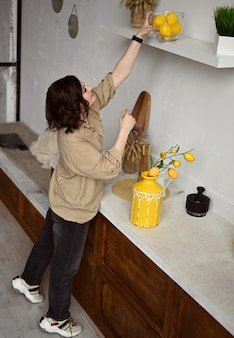 Belle fille dans une cuisine beige avec des citrons jaunes style sicilien italie