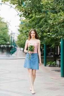Belle fille dans un haut rose délicat et une jupe en jean à l'extérieur. la jeune fille tient un bouquet dans ses mains et marche