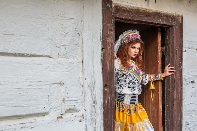 Belle fille dans une hutte en costume national slave.