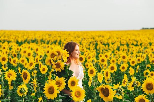 Belle fille dans un immense champ jaune de tournesols.