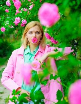 Belle fille dans le jardin fleuri. femme sensuelle au parc avec des roses roses.