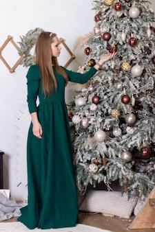 La belle fille dans une longue robe verte se tient près de l'arbre de noël