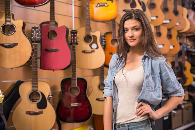 Belle fille dans un magasin de musique avec des guitares espagnoles