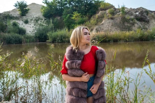 Belle fille dans un manteau de fourrure et un t-shirt et un short rouge clair posant au bord du lac par une chaude journée d'automne