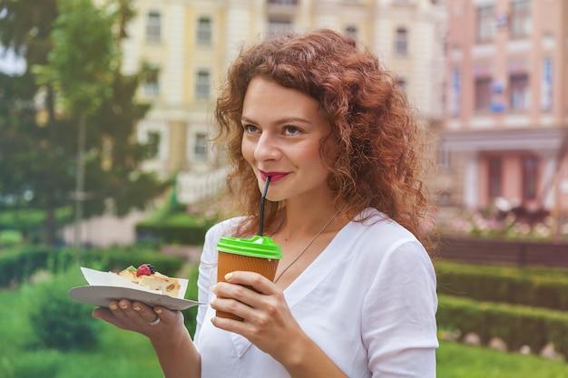 Une belle fille dans le parc boit une tasse de café dans une tasse en papier à travers une paille et tient