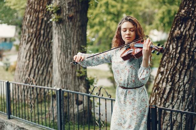 Belle fille dans un parc d'été avec un violon