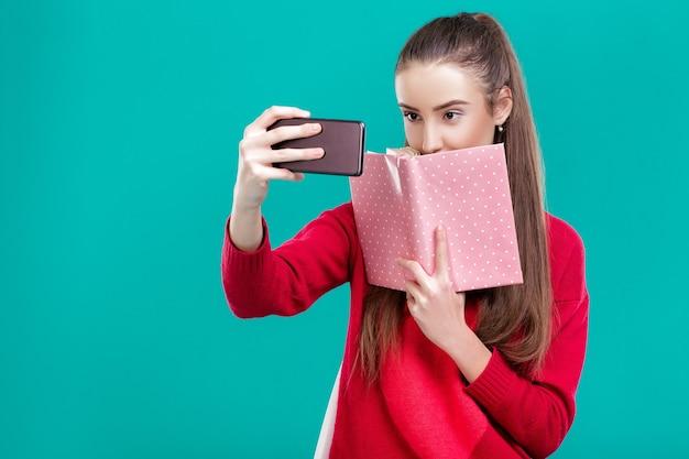 Belle fille dans un pull rouge lit un livre et utilise un smartphone pour selfie