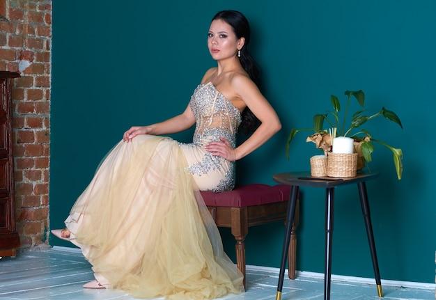 Belle fille dans une robe blanche chic dans une pièce aux murs turquoise.