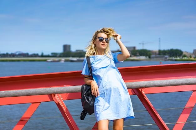 Belle fille dans une robe bleue posant sur le pont