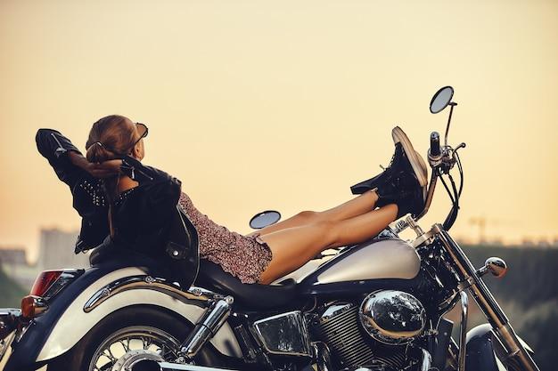 Belle fille dans une robe courte et des bas se trouve de manière séduisante sur une moto coûteuse dans le contexte de la nature par temps brumeux
