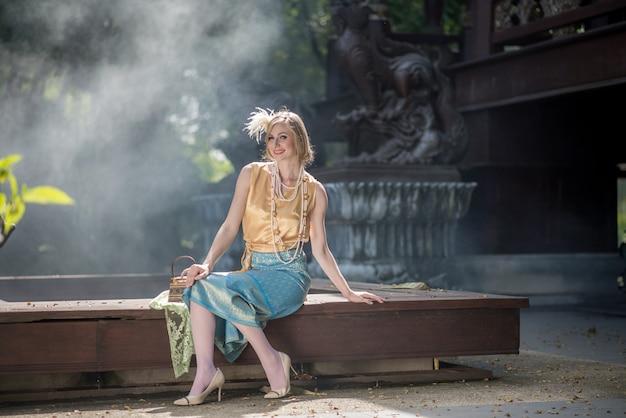 Belle fille dans la robe lumineuse nationale thaïlandaise avec le voyage oriental de maquillage en thaïlande