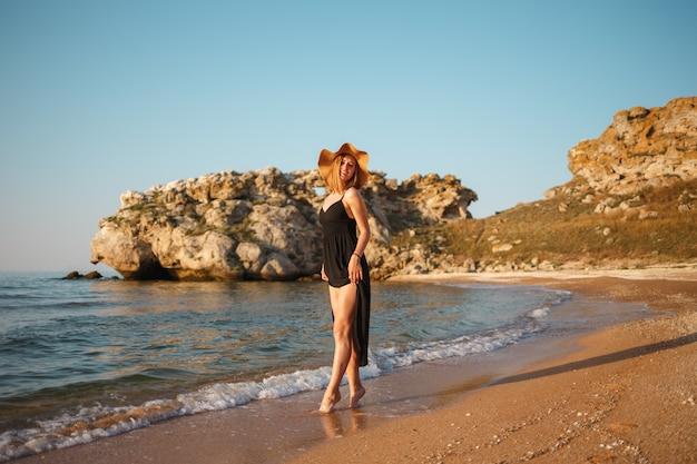 Belle fille dans une robe noire et un chapeau se promène le long du rivage de sable de la mer au coucher du soleil