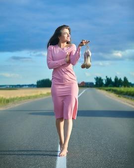 Belle fille dans une robe rose marche pieds nus le long d'une route vide à l'extérieur de la ville