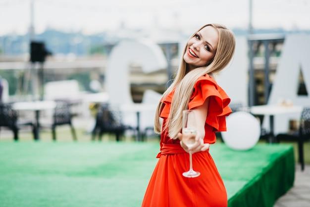 Belle fille dans une robe rouge avec une coupe de champagne
