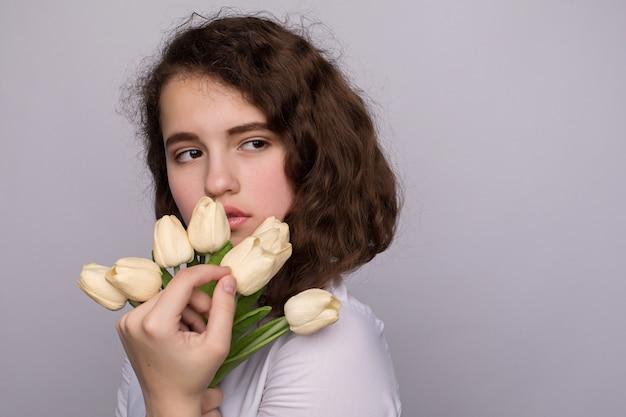 Belle fille dans la robe avec des tulipes fleurs dans les mains sur un fond clair