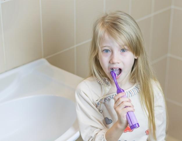 Belle fille dans la salle de bain avec une brosse à dents électrique.
