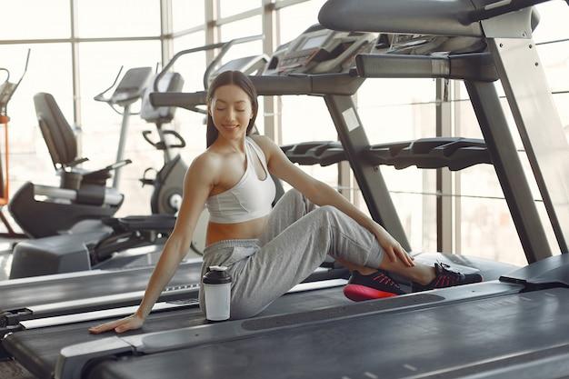 Une belle fille dans une salle de sport sur une piste de course