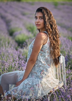 Belle fille dans un sarafan blanc est assise sur une chaise en bois et pose au milieu d'un champ de lavande.