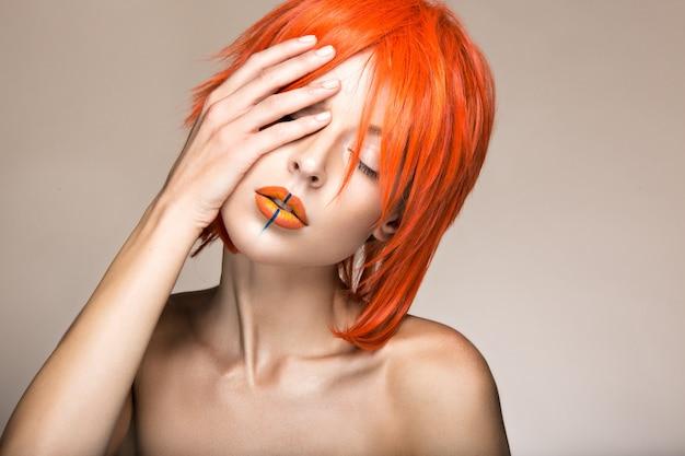 Belle fille dans un style cosplay perruque orange avec des lèvres créatives lumineuses.