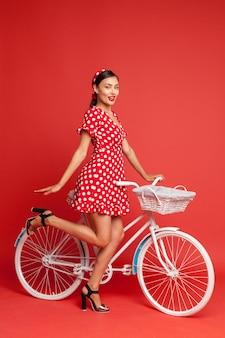 Belle fille dans un style pin-up avec un vélo