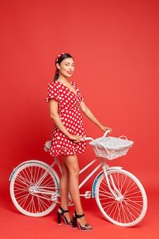 Belle fille dans un style pin up avec un vélo