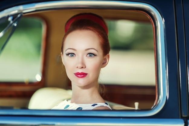 Belle fille dans un style rétro et une voiture ancienne