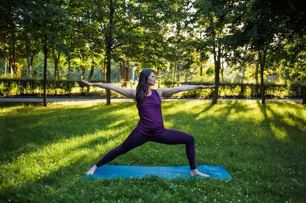Une belle fille dans un survêtement effectue des exercices de yoga sur un tapis au coucher du soleil sur la nature