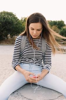 Belle fille dans un t-shirt rayé, écouter de la musique sur la plage