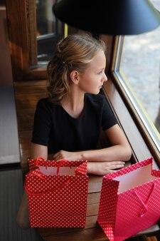 Belle fille dans un tram avec des paquets colorés