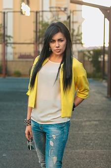 Belle fille dans une veste jaune et un jean détient des lunettes