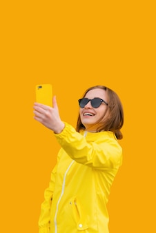 Une belle fille dans une veste jaune prend un selfie sur fond orange