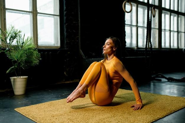 Belle fille dans un vêtement de sport jaune fait du yoga en respirant correctement la salle de sport moderne