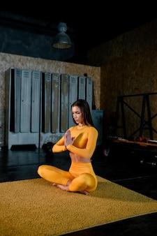 Belle Fille Dans Un Vêtement De Sport Jaune Fait Du Yoga En Respirant Correctement Une Salle De Sport Moderne Photo Premium