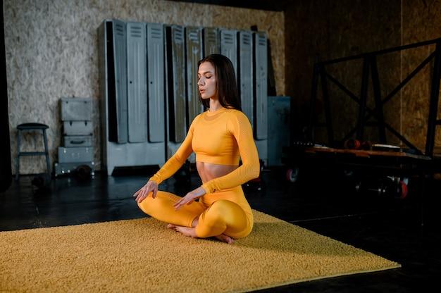 Belle fille dans un vêtement de sport jaune fait du yoga en respirant correctement une salle de sport moderne
