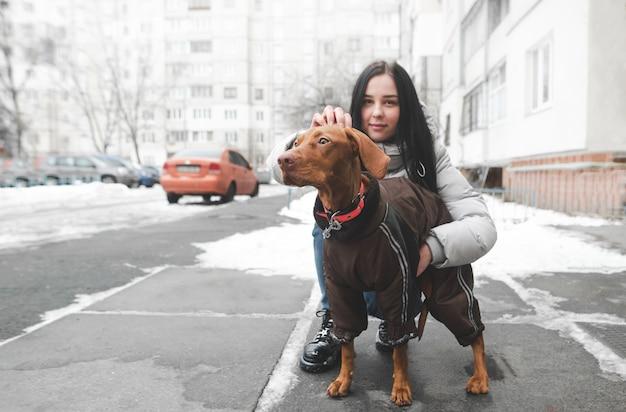 Belle fille dans des vêtements chauds avec un beau chien assis dans la cour et caressant un animal de compagnie