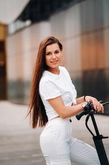 Belle fille dans des vêtements élégants blancs sur un scooter électrique dans la ville