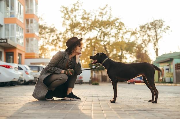 Belle fille dans des vêtements élégants et chapeau jouant avec un chien dans la rue