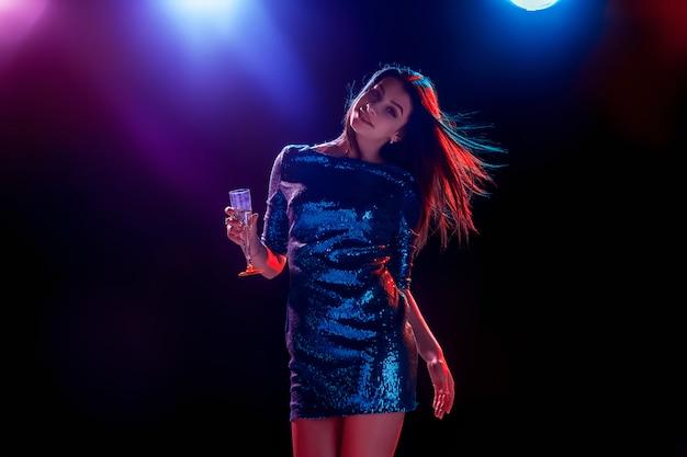 La belle fille dansant à la fête en buvant du champagne