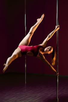 Belle fille danse sur un pylône.