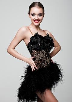Belle fille de danseuse de salon dans une robe noire élégante pose sur gris