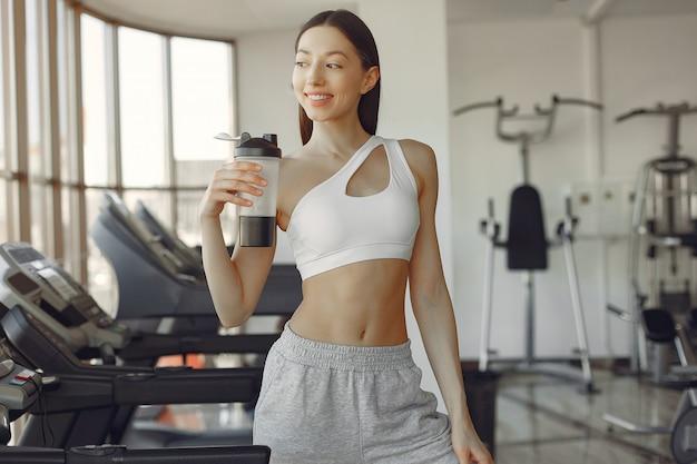Une belle fille debout dans une salle de sport avec une bouteille d'eau