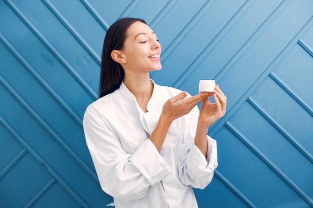 Belle fille debout dans un studio avec de la crème