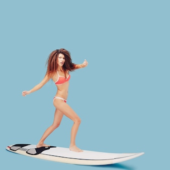 Belle fille debout sur une planche de surf