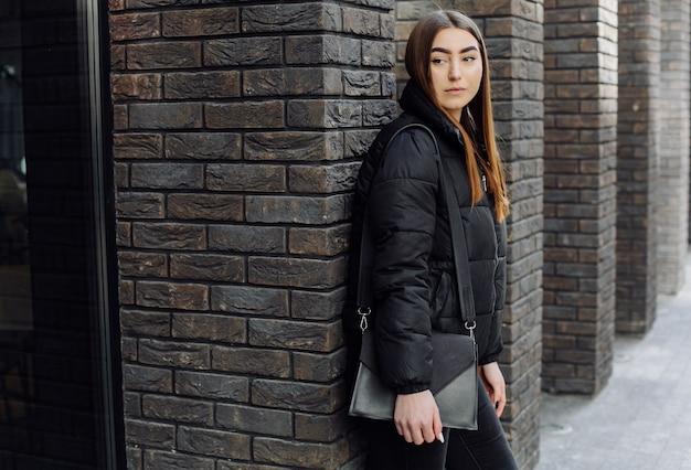 Belle fille debout près du mur et pose