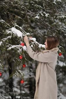 Belle fille décore le sapin de noël avec des boules rouges dans la forêt. bois d'hiver. l'hiver. joyeux noël