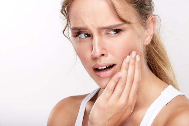 Belle fille avec des dents blanches comme neige sur fond de studio blanc, concept de dentisterie, sourire parfait, douleur, douleur dentaire, dents sensibles, regardant à droite.