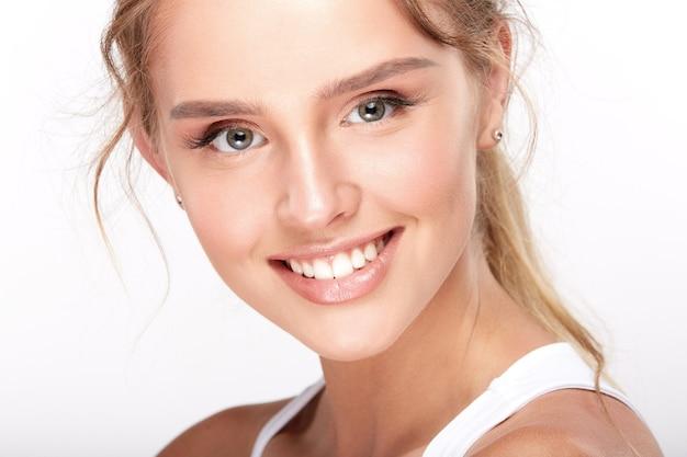 Belle fille avec des dents blanches comme neige sur fond de studio blanc, concept de dentisterie, sourire parfait.