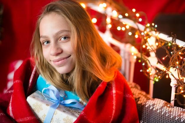Belle fille d'une dizaine d'années, posant pour un photographe dans un intérieur de noël