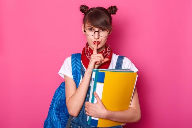 Belle fille avec le doigt sur les lèvres connaît un secret très impuissant. écolière avec des grappes sur la tête, avec un bandana rouge sur le cou, porte un t-shirt blanc et une salopette en jean. l'élève revient à l'école.