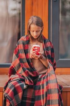 Belle fille avec du cacao chaud profitant de la journée d'automne sur la terrasse